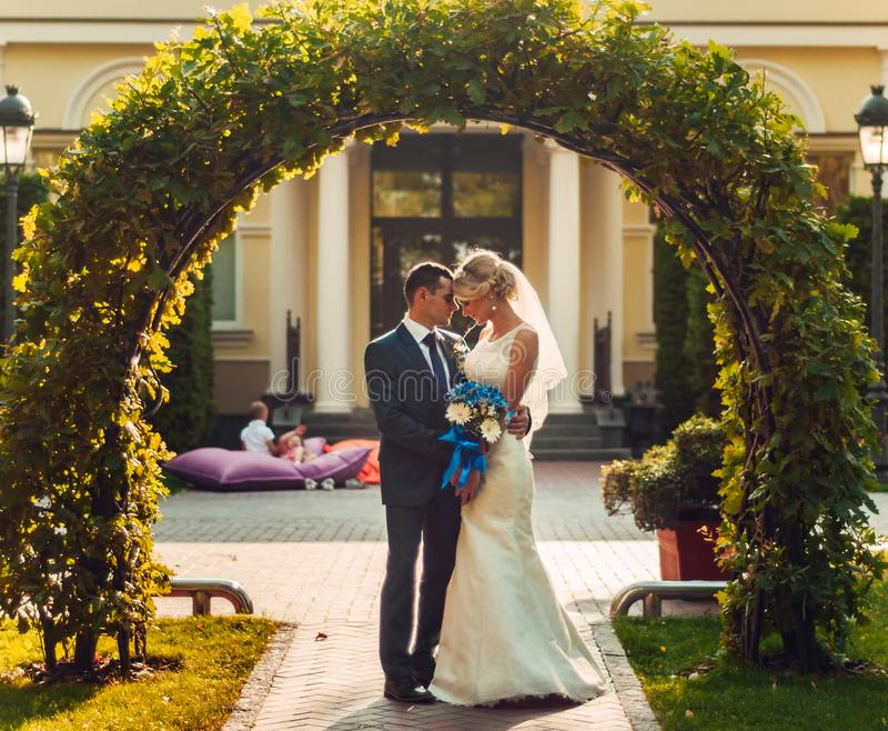 fair-haired bride with a bouquet of flowers in her hands and her fiance are standing near a natural arch royalty free stock photos
