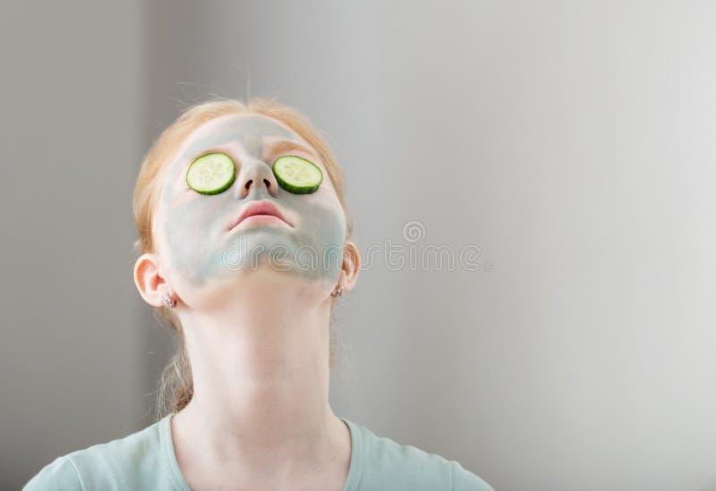 Teen girl puts on face mask. Fair-haired teen girl puts on face mask stock photos