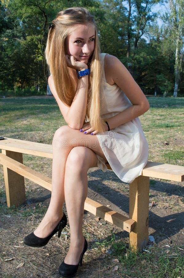 Fair-haired woman in a park on a bench royalty free stock image