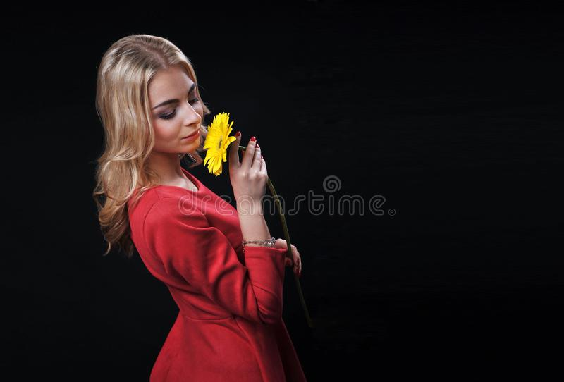The fair-haired young girl woman on a black background with a bouquet branch of yellow chrysanthemums in hands. Looks in a shot and smiles laughs royalty free stock photo