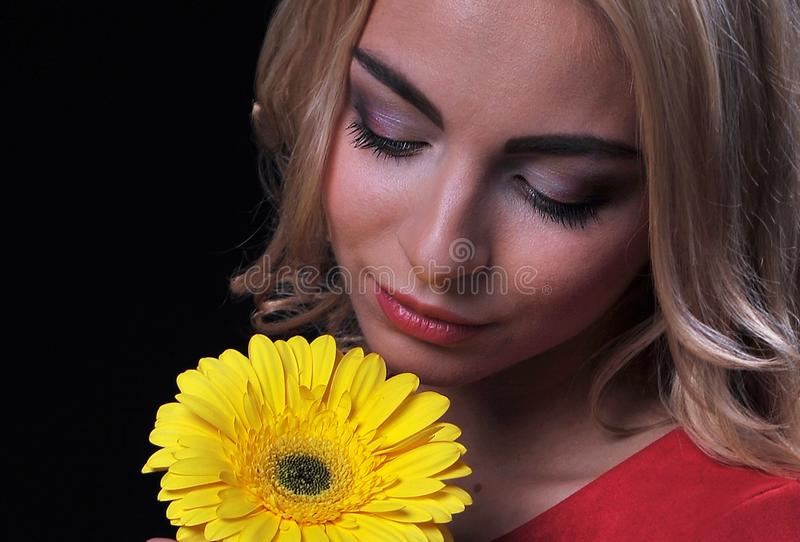 The fair-haired young girl woman on a black background with a bouquet branch of yellow chrysanthemums in hands. The fair-haired young girl woman on a yellow royalty free stock photo