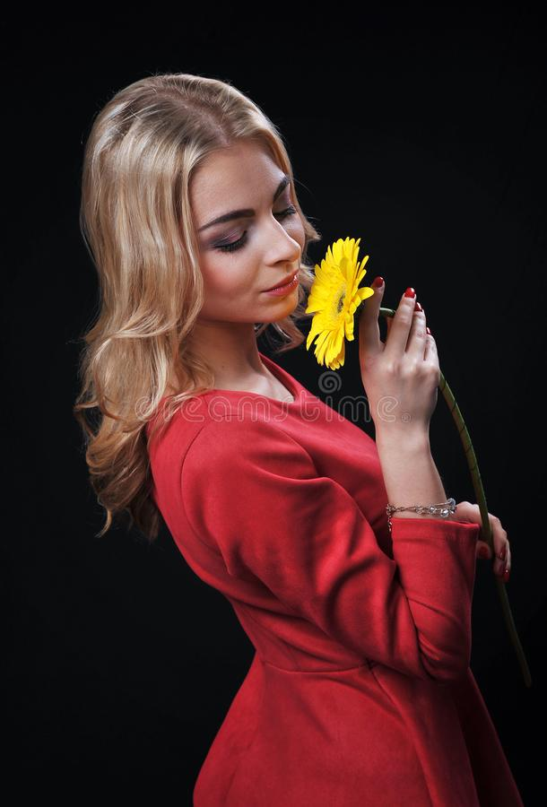 The fair-haired young girl woman on a black background with a bouquet branch of yellow chrysanthemums in hands. Looks in a shot and smiles laughs stock image