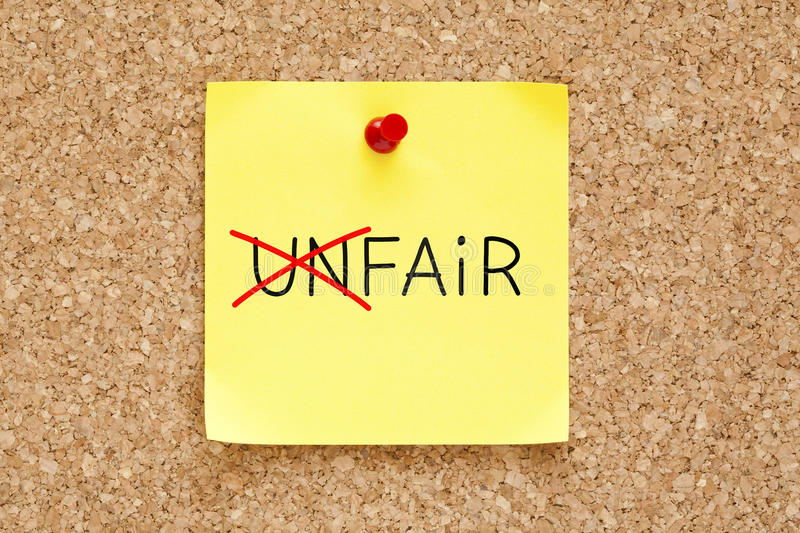 Fair Not Unfair Sticky Note. Turning the word Unfair into Fair with red marker on yellow sticky note pinned with red push pin stock image