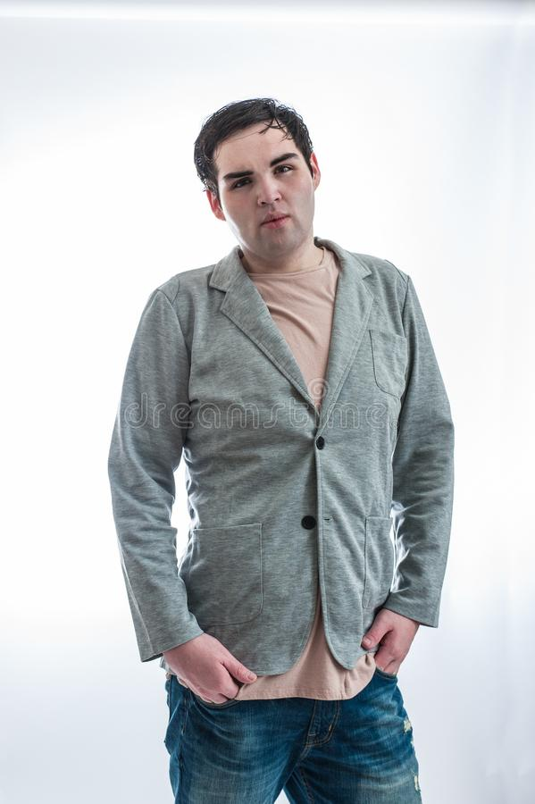 College male rocking the jacket. Fair skinned young man in sports jacket posed with hands in pants pockets stock photos
