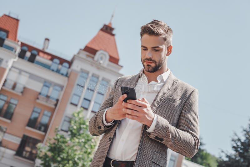 Faire beaucoup L'homme châtain sérieux regarde dans son téléphone tout en se tenant en parc Il va travailler photographie stock