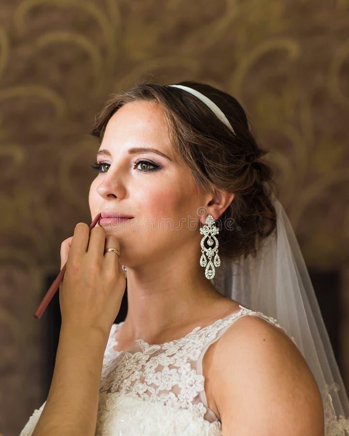 Faire d'artiste de maquillage compensent la jeune belle jeune mariée appliquant le maquillage de mariage photographie stock