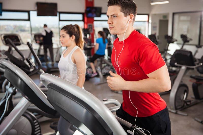 Faire d'homme cardio- et écouter la musique image stock