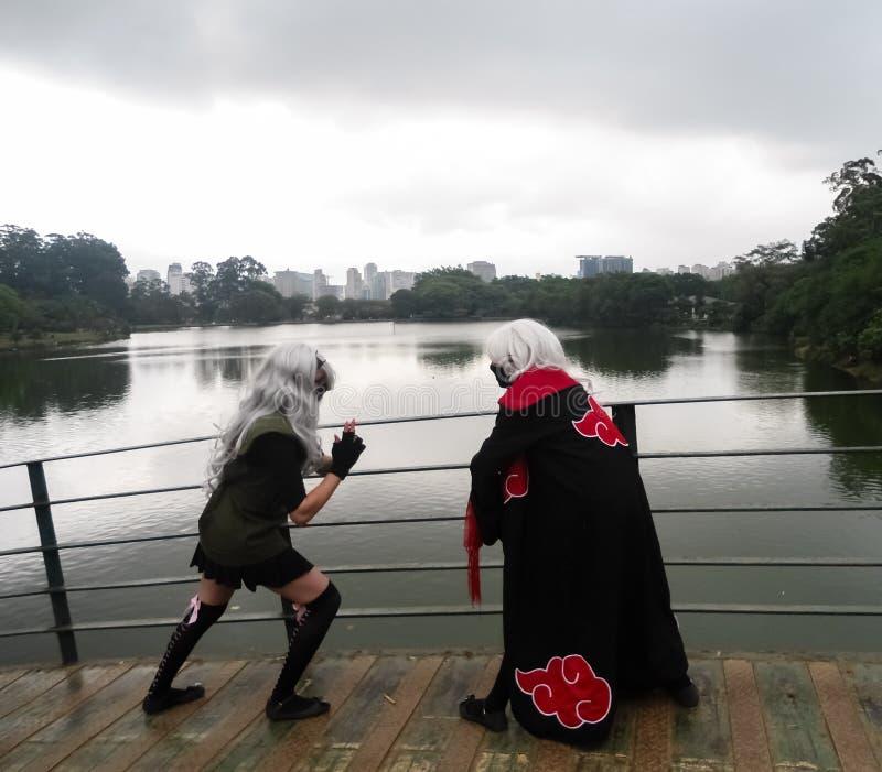 Faire de couples de jeune adolescent cosplay avec la robe noire et les perruques blanches Costume d'Anime photos libres de droits