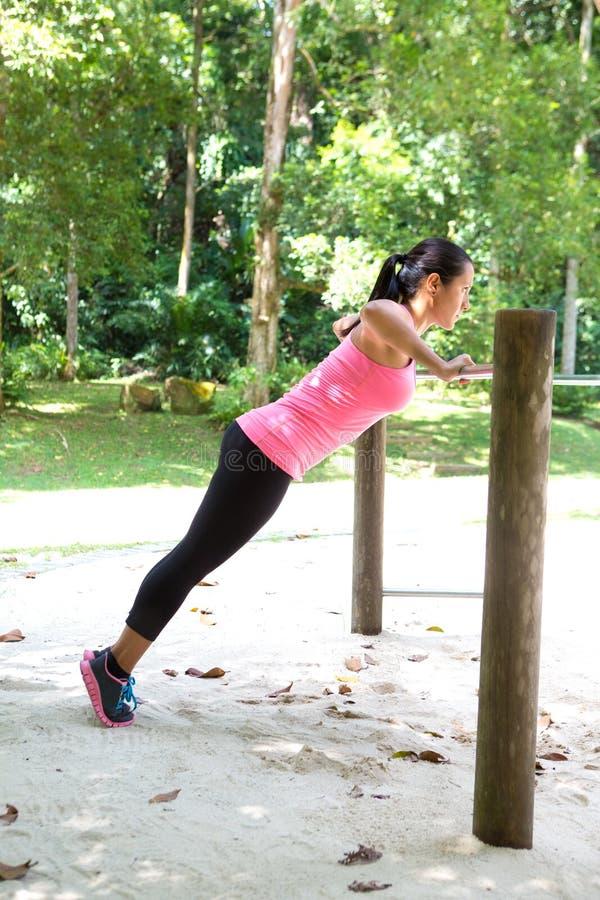 Faire de femme soulèvent sur la barre en parc extérieur d'exercice photographie stock libre de droits