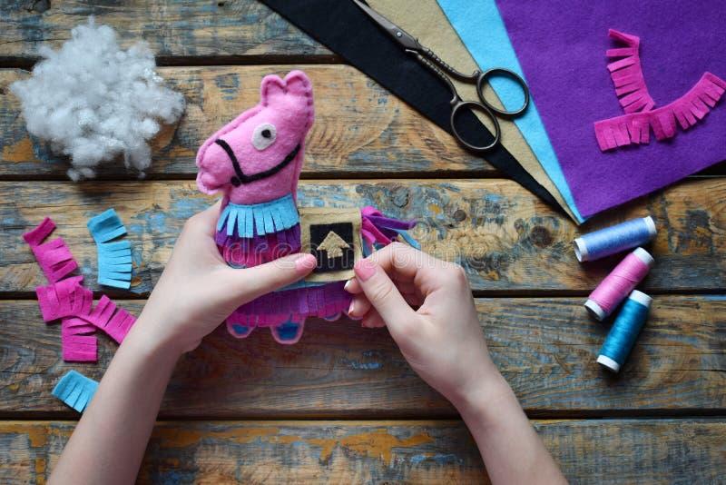 Faire de l'agneau rose Coudre des jouets de feutre de vos propres mains Concept DIY pour les enfants L'artisanat Étape 5 Décorer  image stock