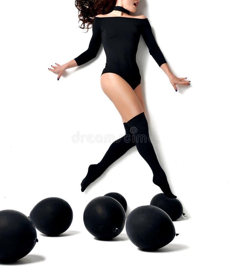 Faire de la lévitation sautant de marche de femme au-dessus des ballons noirs photo libre de droits
