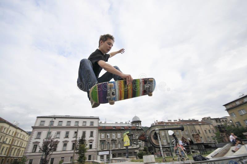 Faire de la planche à roulettes de pratique de garçon photo libre de droits