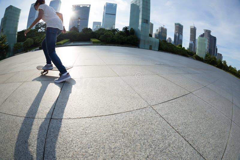 Faire de la planche à roulettes à la ville de lever de soleil photographie stock libre de droits