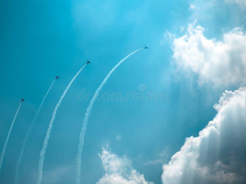 Faire de quatre avions acrobatique aérien sur le ciel nuageux bleu Représentation cubaine de manoeuvre de huit avions photographie stock libre de droits