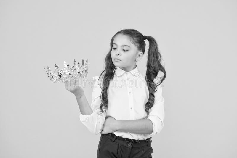 Faire de son bal de promo un air super spécial Une future reine du bal Petit enfant mignon tenant la couronne d'or pour le bal de image libre de droits