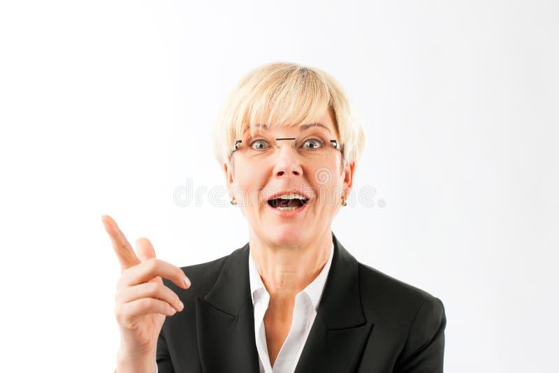 Faire des gestes mûr heureux de femme d'affaires image stock
