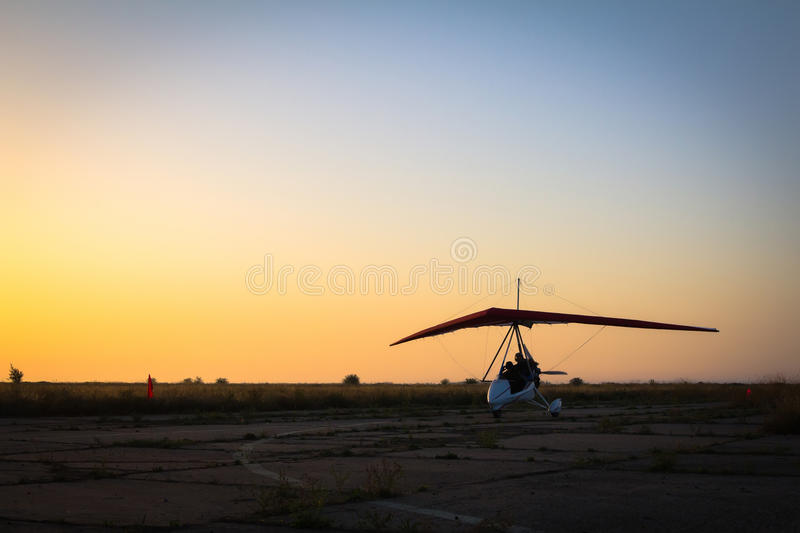 Faire du deltaplane, se tenant à l'aube sur la piste photo stock