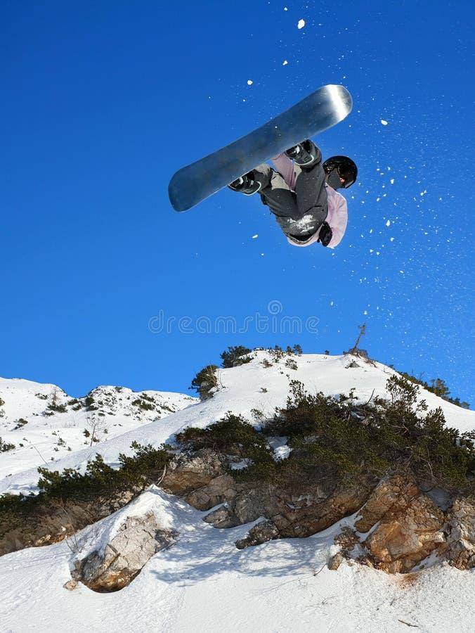 Faire du surf des neiges le surfeur de surf des neiges au saut photo libre de droits