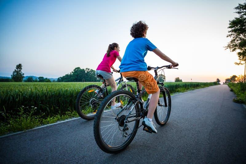 Faire du vélo de fille et de garçon photographie stock libre de droits