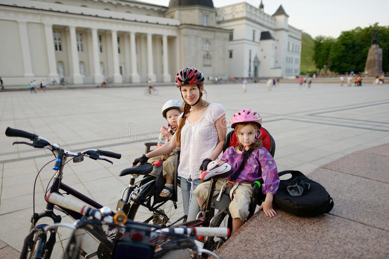 Faire du vélo urbain - jeune mère dans une ville photo libre de droits