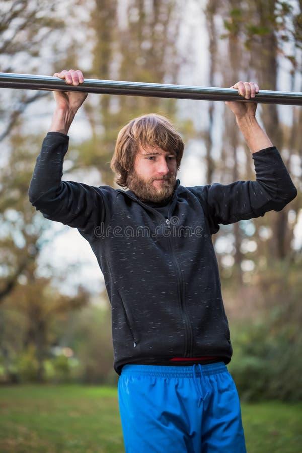Faire folâtre de jeune homme tirent vers le haut l'exercice sur la barre horizontale images stock
