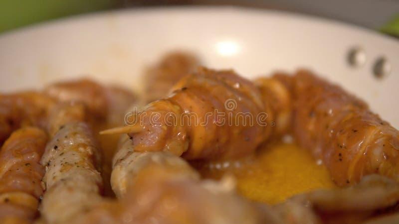 Faire frire des brochettes d'un porc dans la casserole sur la cuisinière à gaz image stock