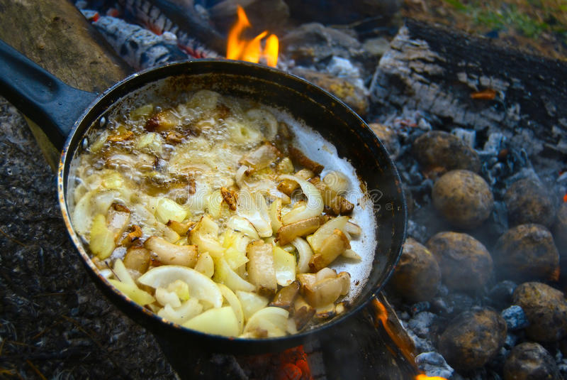 Faire frire des pommes de terre à l'oignon sur le feu images libres de droits