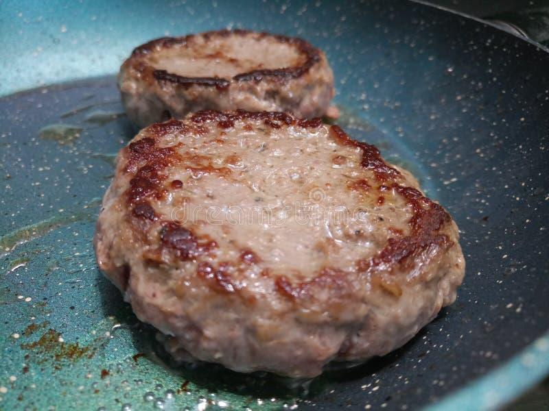 Faire frire juteux de deux hamburgers de boeuf photo stock