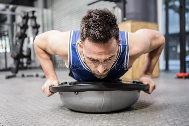 Faire musculaire d'homme soulèvent sur la boule de bosu images stock