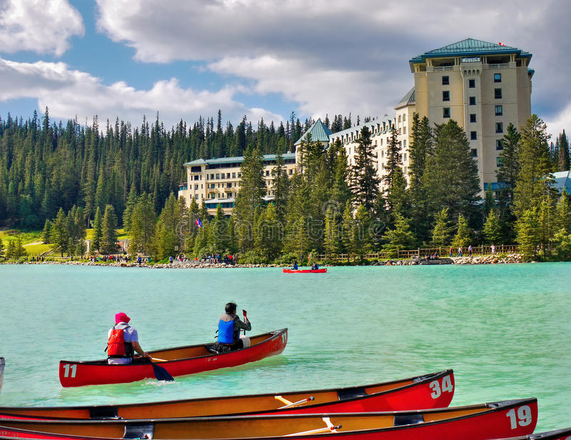 Fairmont Chateau Lake Louise. The Fairmont Chateau over Lake Louise and visitors on boat. Banff National Park, Alberta, Canada stock image