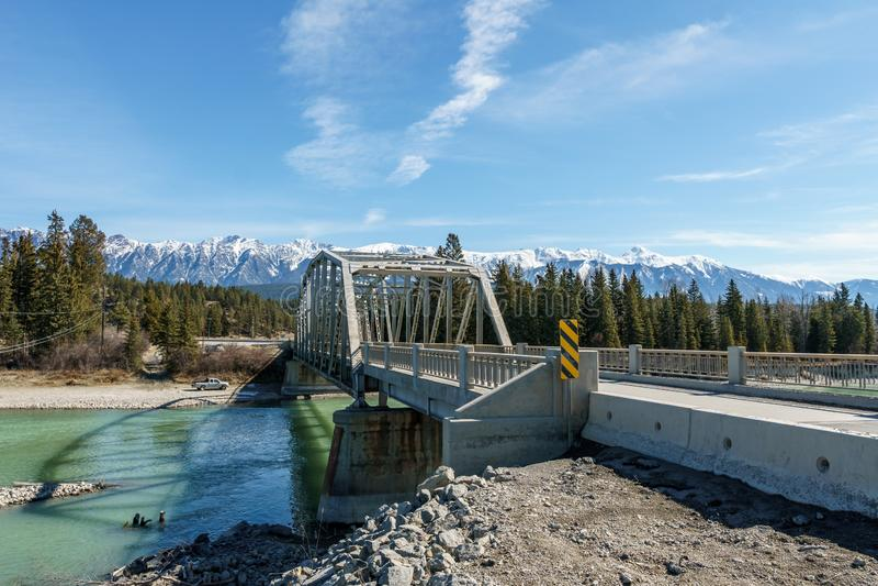 Fairmont Hot Springs, CANADÁ - 22 DE MARÇO DE 2019: ponte do metal sobre o rio com água verde fotos de stock