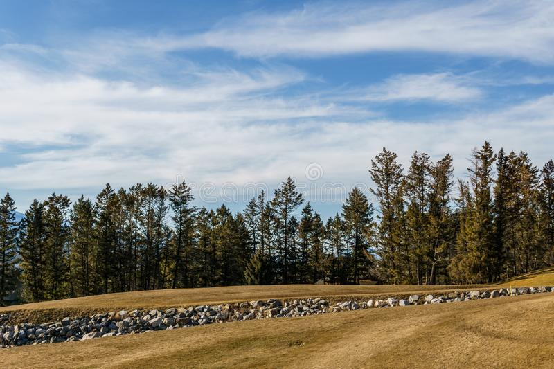 FAIRMONT HOT SPRINGS, CANADA - MARCH 22, 2019: Golf Course field in small town in rocky mountains sunny afternoon stock image