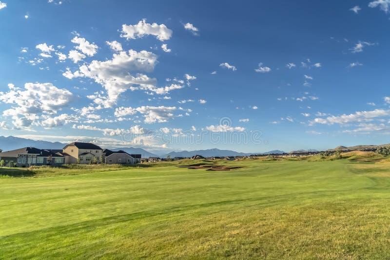 Fairway di un campo da golf in vista di case e montagne sullo sfondo immagini stock