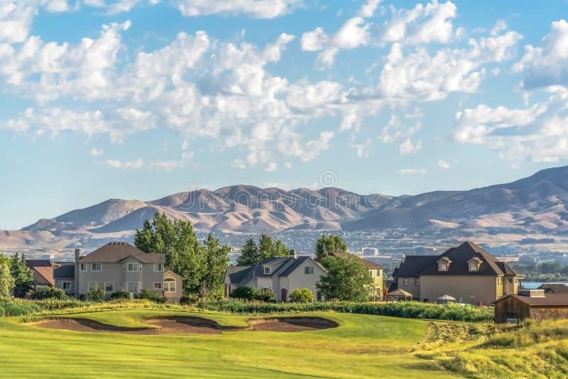 Fairway e bunker di campo da golf di fronte a case con vista sul lago e sulle montagne fotografia stock