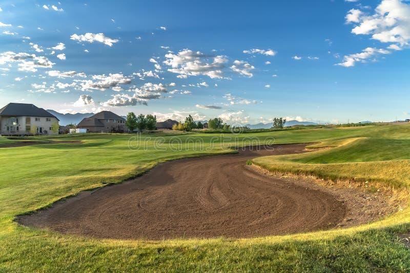 Fairway e bunker su un campo da golf con case e montagne a distanza fotografia stock