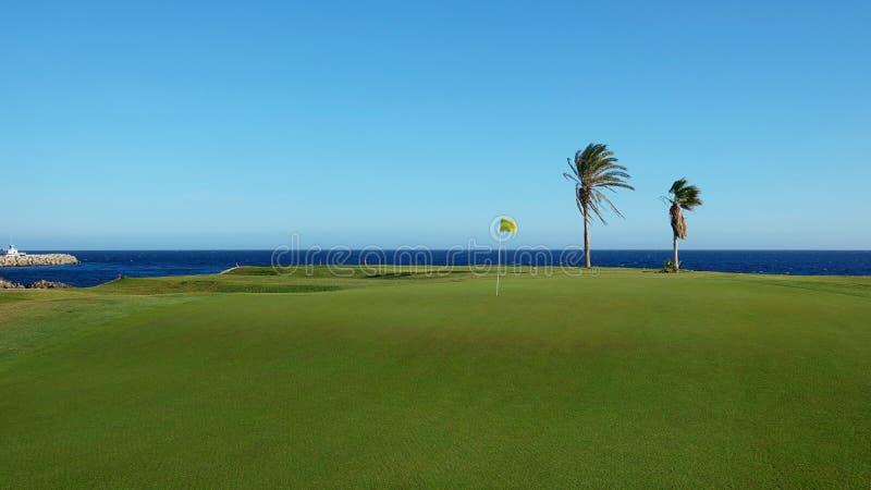 Fairway tropical bonito do campo de golfe com um flagstick amarelo, na borda do Oceano Atlântico foto de stock royalty free