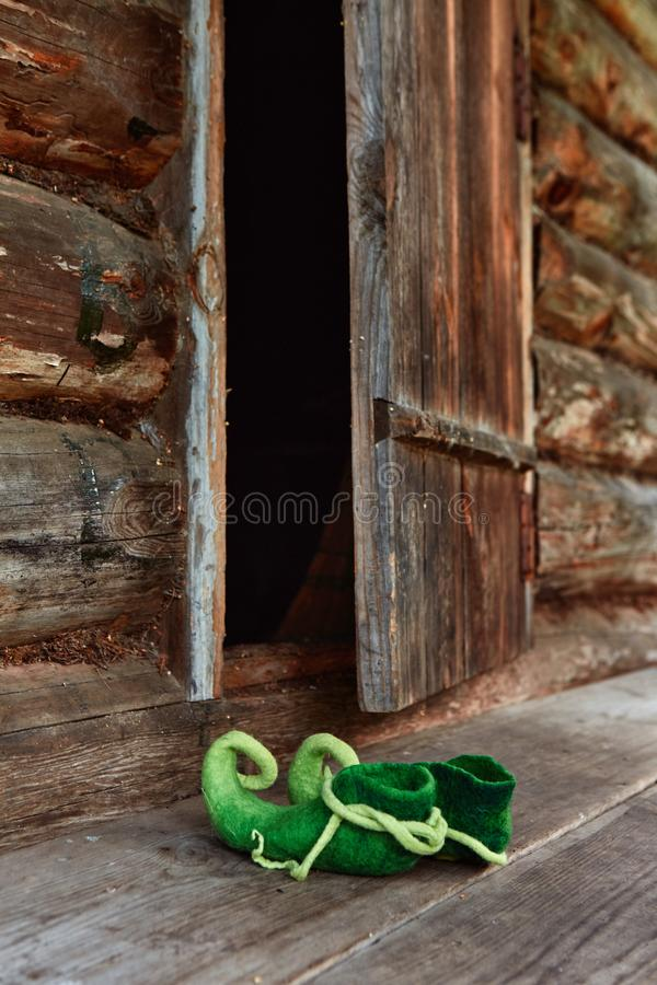Fairy creature elf or forest dwarf left his shoes on the threshold of an old wooden house near the front door stock photos