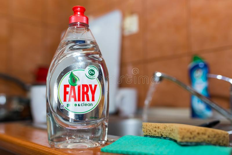 Fairy dishwashing liquid on kitchen sink, flowing tap water in the background. royalty free stock images