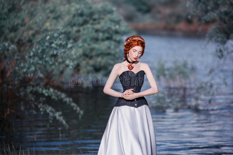 Fairy edwardian princess with red necklace and hairstyle on nature background. Fairy queen in white renaissance dress against. Backdrop of blue water. Princess royalty free stock photo