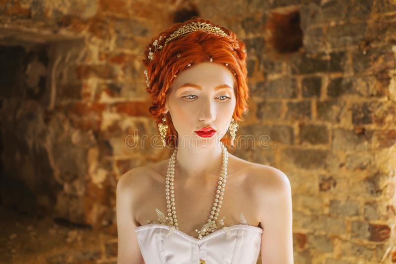 Fairy edwardian redhead princess with freckles in the old castle. Fabulous rococo queen against backdrop of stone wall. Edwardian royalty free stock image