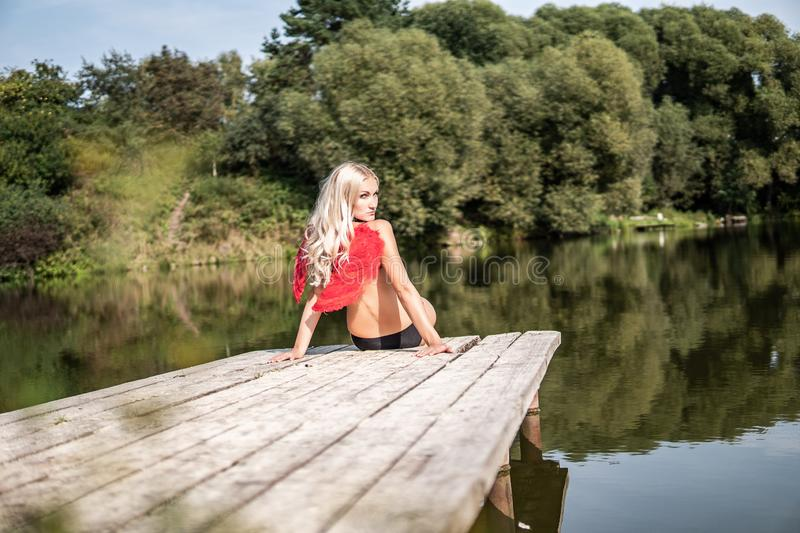 Fairy girl in Angel Red Wings sits on the quay on the river bank. gently turning head stock images