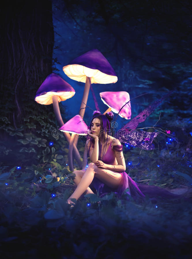 Free Fairy Sitting Under Huge Mushrooms. Royalty Free Stock Photography - 75258517