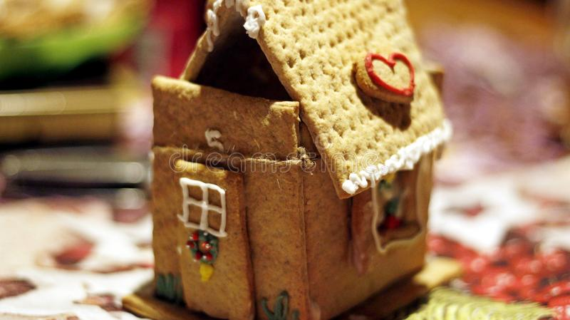 Fairytale accent on the holiday table in the form of a gingerbread house. The fairy-tale accent on the holiday table in the form of a gingerbread house will make royalty free stock photos