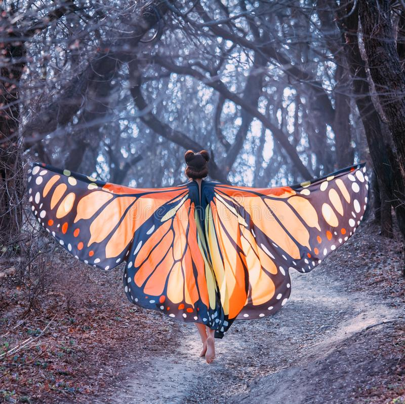 Fairy tale about butterfly, mysterious story of girl with red hair and big light orange wings, lady walks barefoot along royalty free stock images