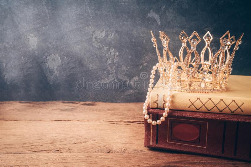 Fairy tale crown and old books on wooden table over black background royalty free stock image