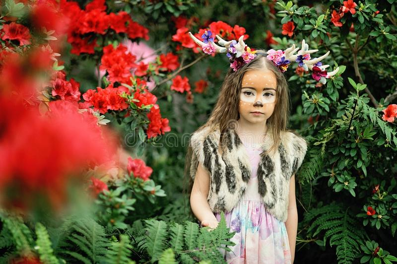 Fairy tale girl. Portrait a little girl in a deer dress with a painted face in the forest. Big antler. Fantasy girl. Springtime. Environment protection. Save royalty free stock photos