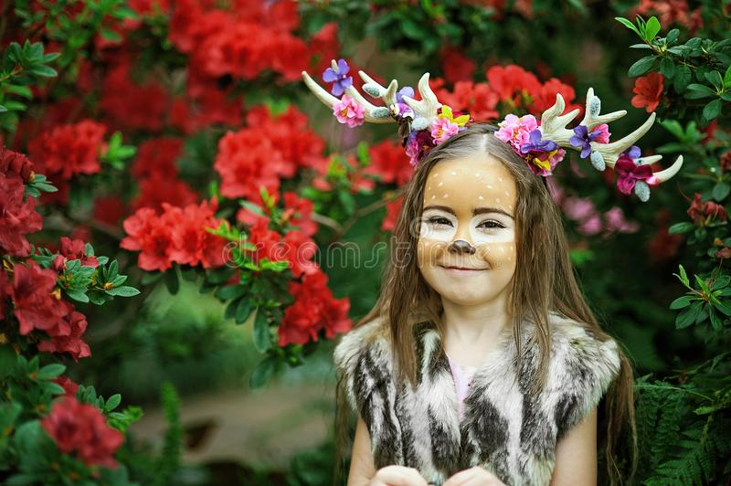 Fairy tale girl. Portrait a little girl in a deer dress with a painted face in the forest. Big brown antler. Fairy tale girl. Portrait a little girl in a deer stock photo