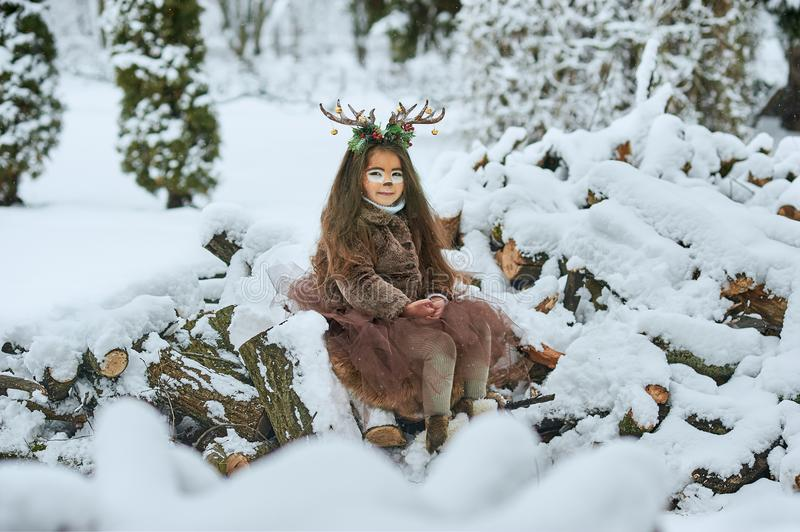 Fairy tale girl. Portrait a little girl in a deer dress with a painted face in the winter forest. Big brown antler royalty free stock photography