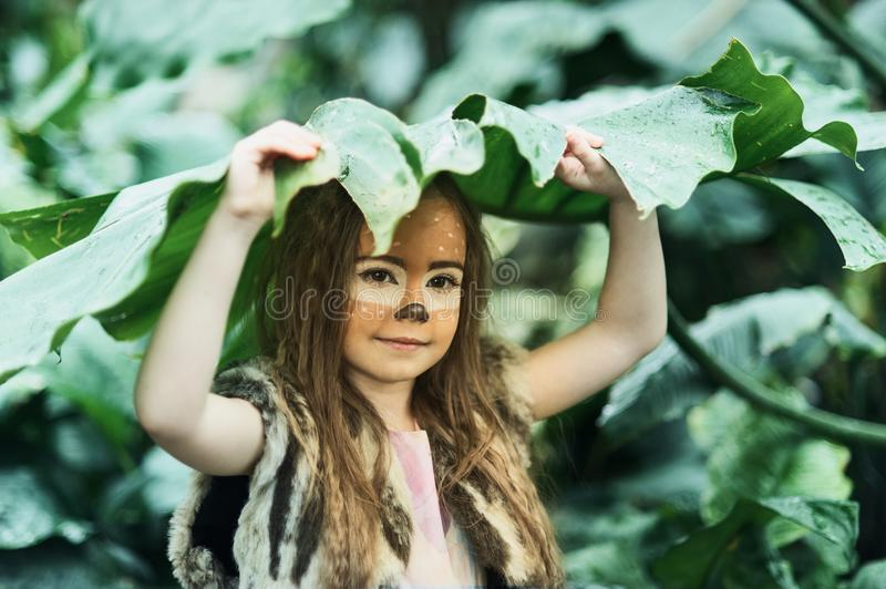 Fairy tale girl. Portrait a little girl in a deer dress with a painted face in the forest. Big antler. Fantasy girl. Springtime. Environment protection. Save stock photos