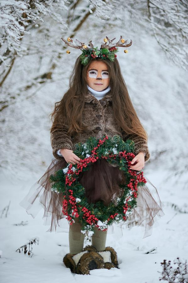 Fairy tale girl. Portrait a little girl in a deer dress with a painted face in the winter forest. Big brown antler. Fantasy girl with christmas wreath. Snowy royalty free stock images